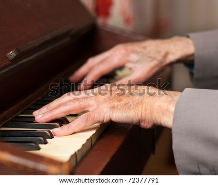 Elderly hands playing on an old harmonium. - stock photo