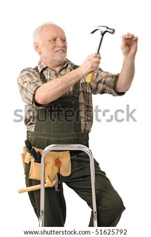 Elderly handyman doing home renovation hammering nail, cutout. - stock photo