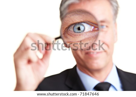 Elderly happy business man looking through a magnifying glass - stock photo