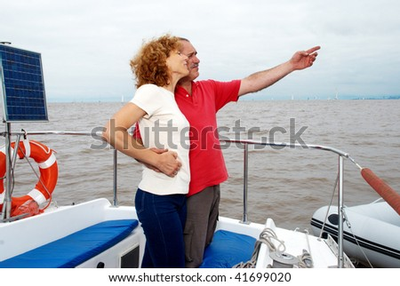 Elderly happy couple onboard the yacht looking in a distance - stock photo