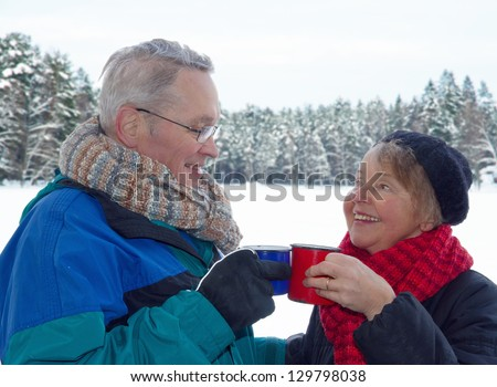 Elderly happy couple toasting with cups of warm drinks, outside in snow winter forest landscape