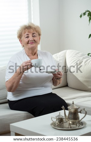Elderly happy lady during her coffee time - stock photo