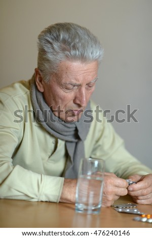 Elderly ill man with pills