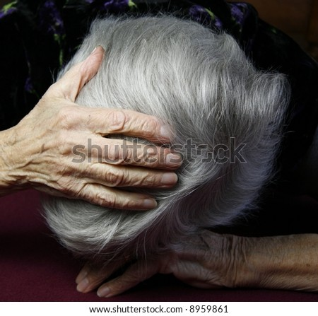 elderly lady holding head in deep depression