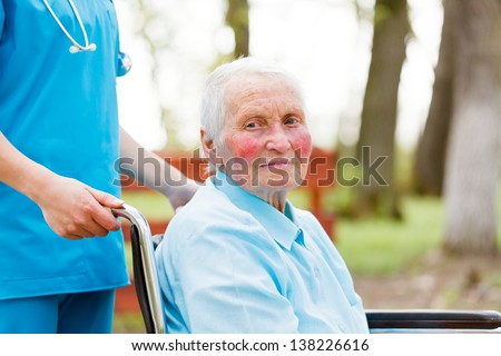 Elderly lady in wheelchair pushed by nurse.
