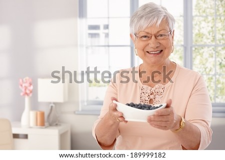 Elderly lady offering a bowl of blueberry, smiling, looking at camera. - stock photo