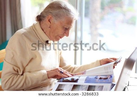 Elderly lady reading magazine. Shallow DOF. - stock photo