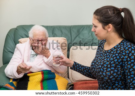 Elderly lady takes bitter medicine while young lady kindly offers her glass of water. Elderly woman sits on pale green lounge with multicolored blanket and pink dressing gown covering her.