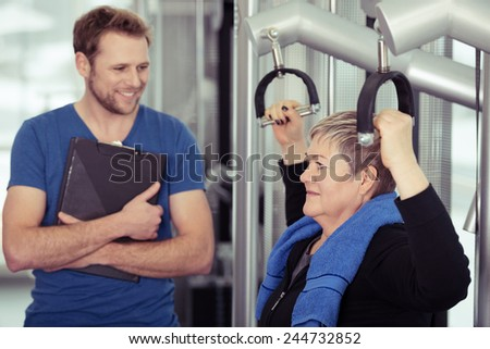 Elderly lady working out with a friendly smiling young male trainer or fitness instructor in a gym in a healthy lifestyle and exercise concept - stock photo