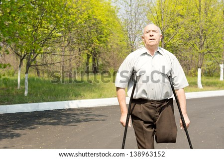 Elderly male amputee balanced on crutches in a rural street with his trousers pinned up to reveal his stump