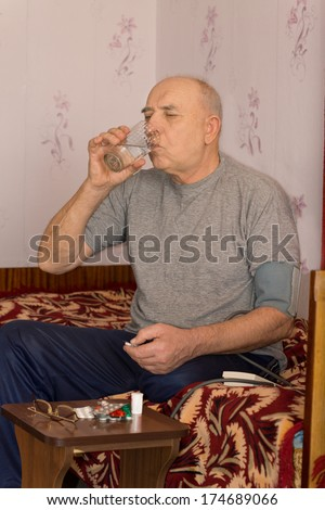Elderly male amputee sitting taking his medication swalling down the tablets with a glass of water - stock photo
