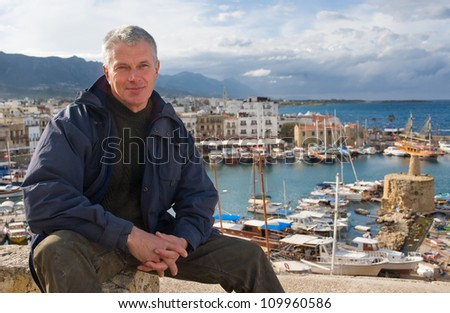 elderly man against the port of Kyrenia - stock photo