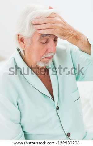 Elderly man checking his temperature - stock photo