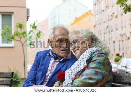 Elderly man confesses his love for an elderly woman on the bench. Modern city. Fancy clothes, holiday wear make up/ Concept of love, passion, date. - stock photo