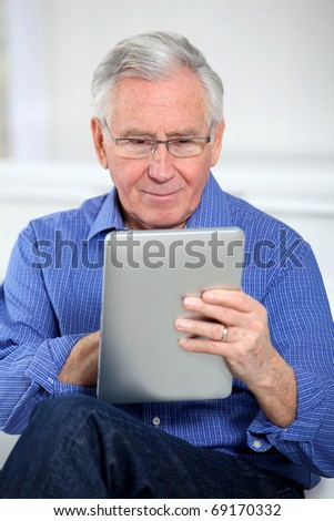 Elderly man connected on internet with electronic tab - stock photo