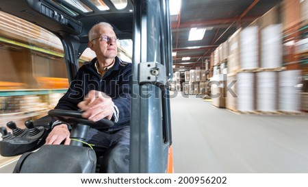 Elderly man driving a forklift through a warehouse where cardboard boxes are stored.  - stock photo
