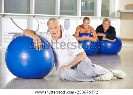 Elderly man exercising with gym ball in health club for rehab - stock photo
