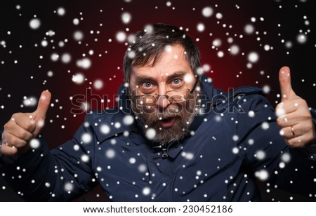 Elderly man gives thumbs down on a red background. Christmas and holidays concept