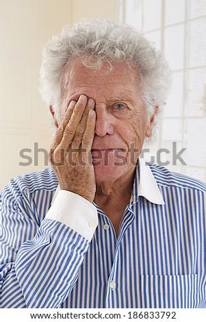 Elderly man holding hand over his aching eye  - stock photo