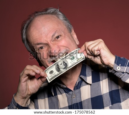 Elderly man holding with pleasure one hundred dollar bill