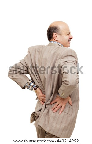 Elderly man holds on lower back and wincing. pain in spine or kidney - stock photo