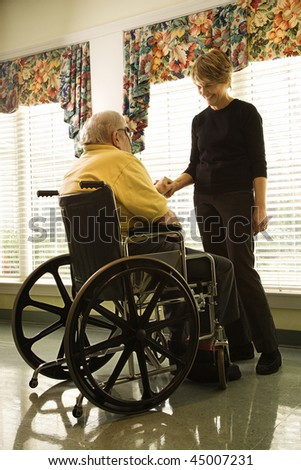 Elderly man in a wheelchair and a young woman stand by a window and hold hands.  Vertical shot. - stock photo