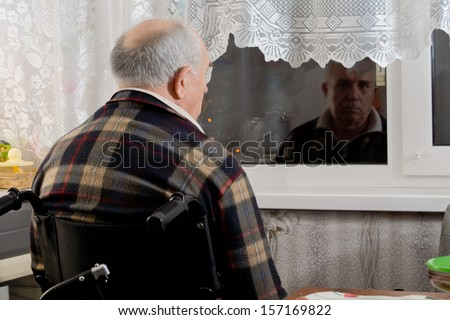 Elderly man in a wheelchair sitting waiting at a window with his back to the camera staring through the glass into the dark night - stock photo