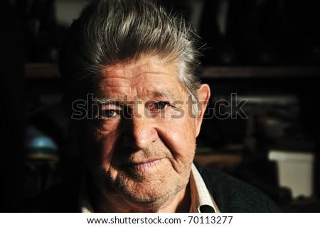 Elderly man in his workshop, portrait - stock photo