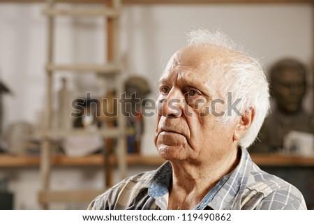 Elderly man in sculptors workshop looking sideways - stock photo