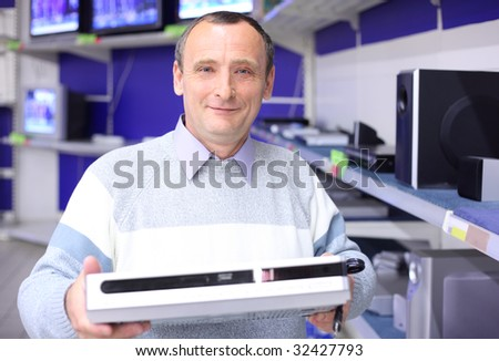 elderly man in shop of radio engineering with dvd-player in hands