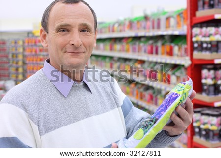 elderly man in shop with package in hands, looking at camera - stock photo