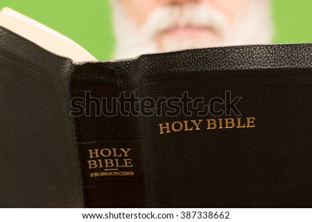Elderly man is holding bible on green background, color and contrast manipulated - stock photo