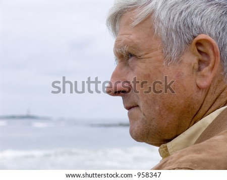 Elderly man looking out over the ocean - stock photo