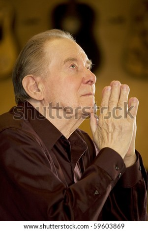 Elderly man looking up while praying in dark church - stock photo