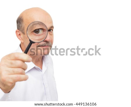 elderly man looks at something through a magnifying glass. - stock photo
