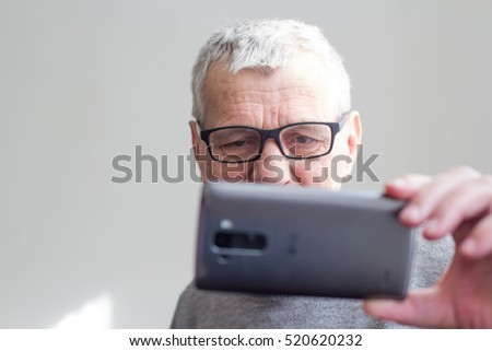 elderly man makes selfie with mobile
