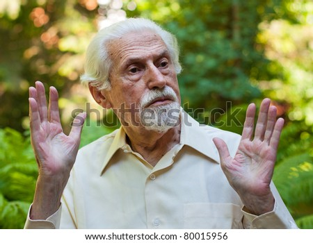 Elderly man making a facial expression of protest. - stock photo