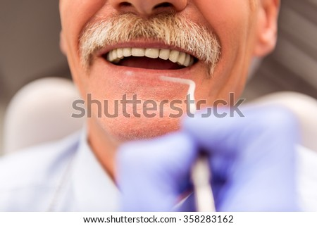 Elderly man on a review of a dentist, sitting in a chair - stock photo