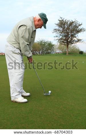 elderly man on the golf putting green - stock photo