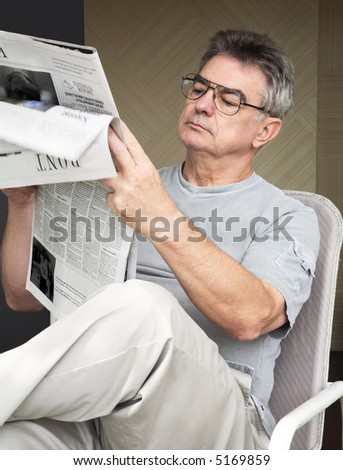 Elderly man reading a newspaper.