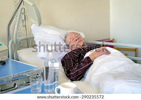 Elderly man recuperating in a hospital lying asleep in a bed on the ward in his pyjamas still wearing his spectacles in health care and medical concept - stock photo