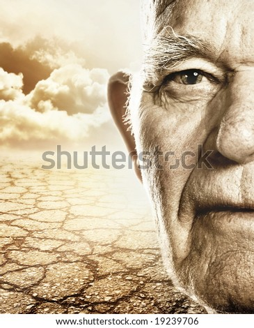 Elderly man's face over dry desert land background - stock photo