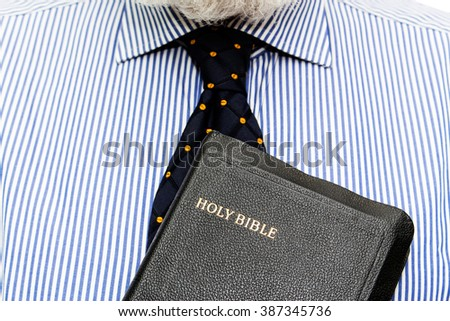 Elderly man, senior, is holding bible on chest, color and contrast manipulated - stock photo