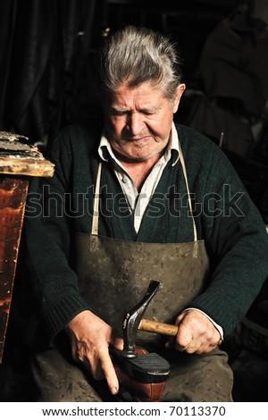 Elderly man, shoemaker repairing old shoe in his workshop - stock photo