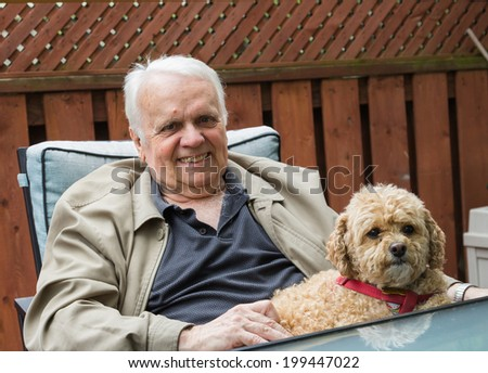 Elderly Man sitting down with his dog - stock photo