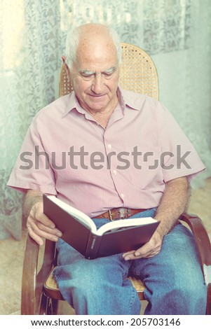 Elderly man sitting in chair reading book at home - stock photo
