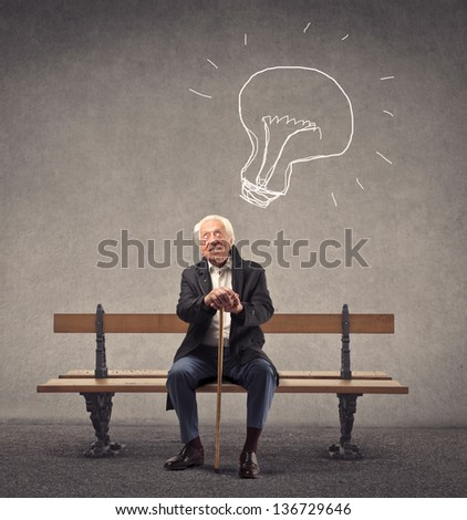 elderly man sitting on a bench has an idea - stock photo