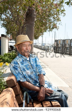 Elderly man sitting on bench and  enjoying