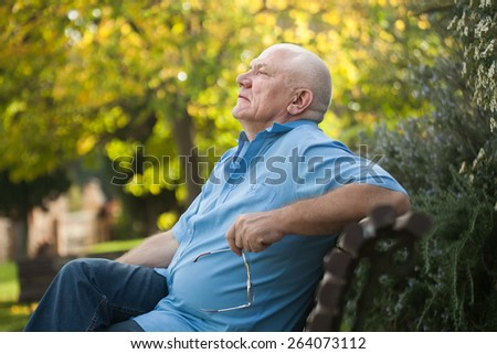 Elderly man sitting on   bench in autumn park.  - stock photo