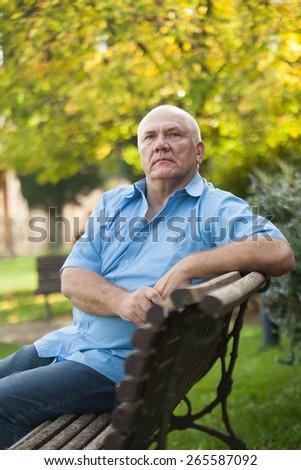 Elderly man sitting on   bench in autumn park.  - stock photo